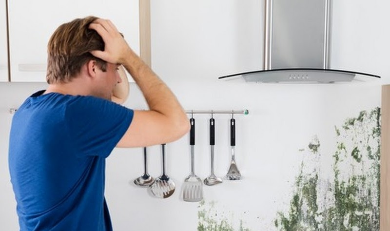 young man looking worried about black mould in his kitchen