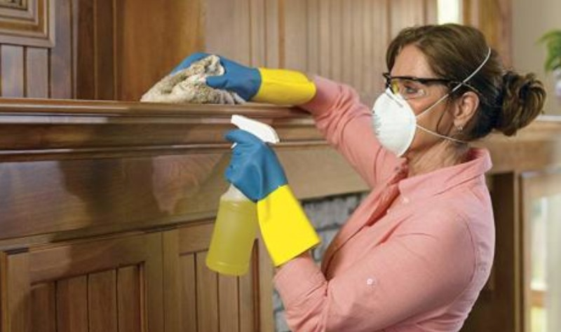 a woman with a mask disinfecting wooden surface with a spray
