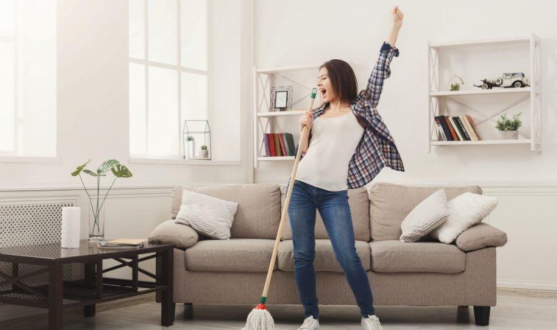 a happy woman holding a broom in her hand