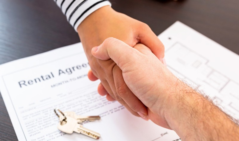 cropped image of property owner and tenant shaking hand after signing a rental agreement