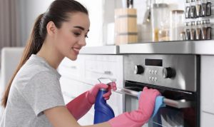 beautiful young woman moping an oven with a cloth