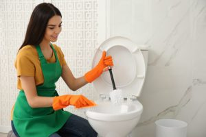 young woman inside a toilet holding toilet brushes in her hands