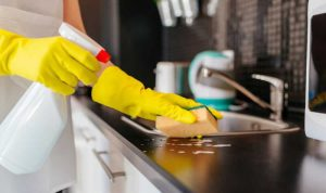 cropped picture of a woman wiping a kitchen counter top with a cloth