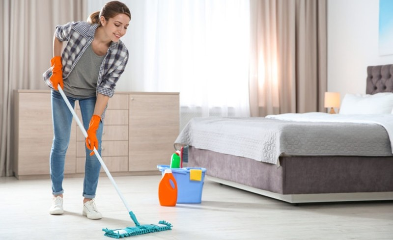 young woman wiping a floor with a wiper