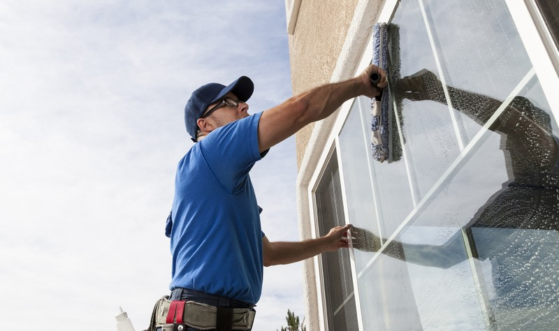 professional wiping a window glass with a wiper