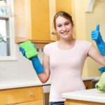 Young woman with a sponge and blue gloves preparing to spruce up her house