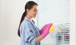 Young woman wiping the window blinds with a cloth rag