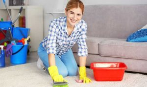 young woman trying to remove stains from a carpet with a brush