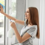 Young woman disinfecting the window glass